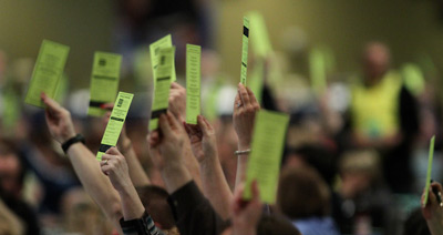 Democracy in action: WEA R.A. delegates raise their voting cards.